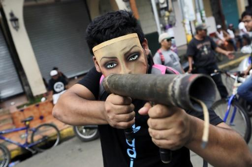 A demonstrator wearing a mask points homemade mortar during a protest in Masaya
