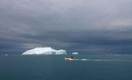 A fishing boat on Greenland's Jacobshavn Bay sails past floating icebergs on August 26, 2007.