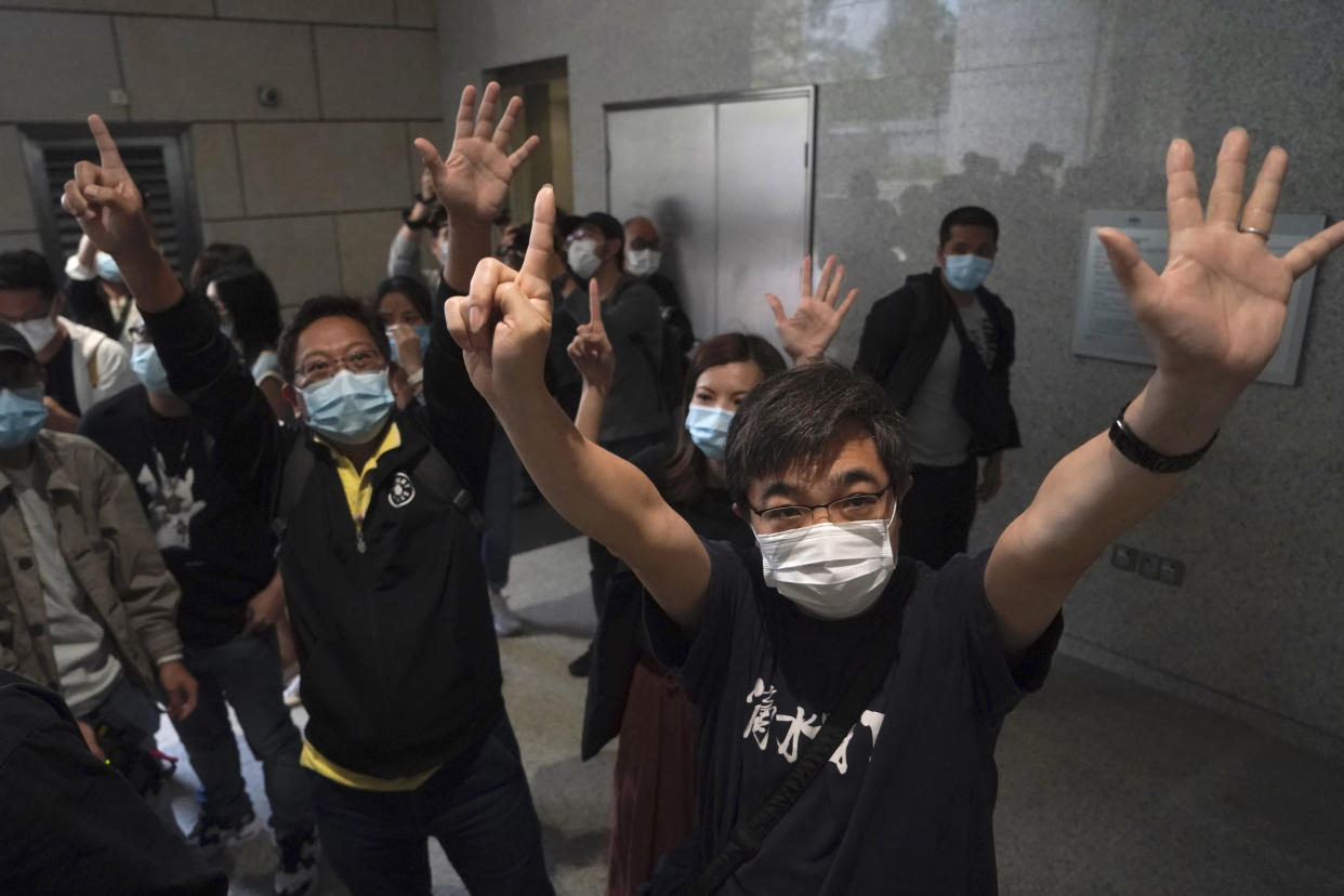 """Protesters gesture with five fingers, signifying the """"Five demands - not one less"""" outside a court in Hong Kong Friday, April 16, 2021. Seven of Hong Kong's leading pro-democracy advocates, including 82-year-old veteran activist Martin Lee and pro-democracy media tycoon Jimmy Lai, are expected to be sentenced Friday for organizing a march during the 2019 anti-government protests that triggered an overwhelming crackdown from Beijing. (AP Photo/Kin Cheung)"""