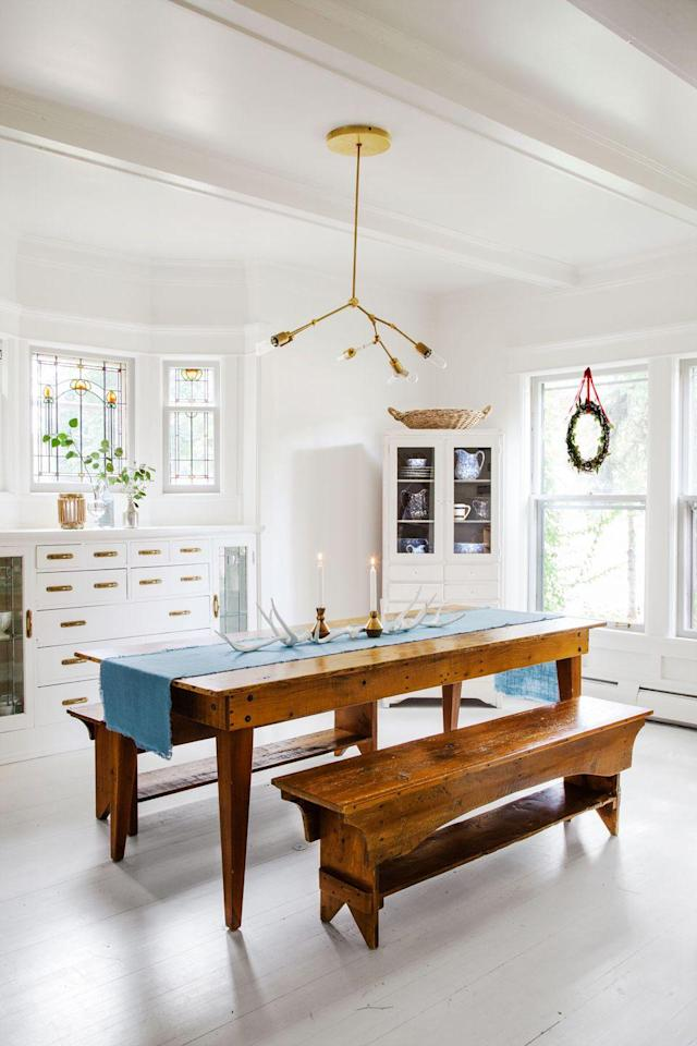 """<p>This designer keeps the dining room table in her <a href=""""https://www.countryliving.com/home-design/house-tours/g2780/jennaea-gearhart-white-christmas-decor/"""" rel=""""nofollow noopener"""" target=""""_blank"""" data-ylk=""""slk:historic Tudor house"""" class=""""link rapid-noclick-resp"""">historic Tudor house</a> simple for the season with a blue runner, brass candle holders, and antlers.</p><p><a href=""""https://www.etsy.com/market/brass_candle_holder"""" rel=""""nofollow noopener"""" target=""""_blank"""" data-ylk=""""slk:SHOP BRASS CANDLE HOLDERS"""" class=""""link rapid-noclick-resp"""">SHOP BRASS CANDLE HOLDERS</a></p>"""