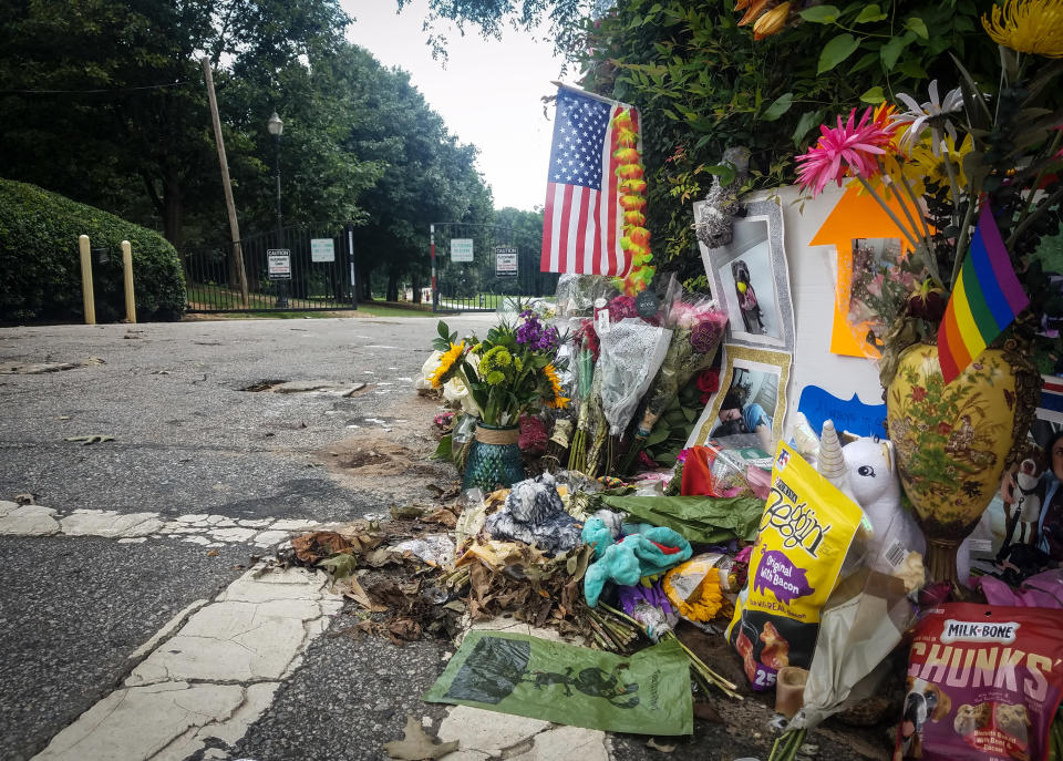 A makeshift memorial to Katherine Janness is seen at the entrance to Piedmont Park on Sunday, Aug. 1, 2021, in Atlanta. Janness, 40, was found stabbed to death in the park in the early hours of July 28. Police say her dog was also killed at the scene. No arrests have been made and the FBI is assisting local authorities in the case. (AP Photo/Ron Harris)