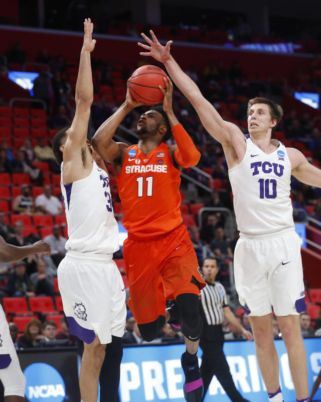 Syracuse forward Oshae Brissett (11) drives on TCU guard Kenrich Williams (34) and Vladimir Brodziansky (10) during the second half of an NCAA men's college basketball tournament first-round game in Detroit, Friday, March 16, 2018. (AP Photo/Paul Sancya)