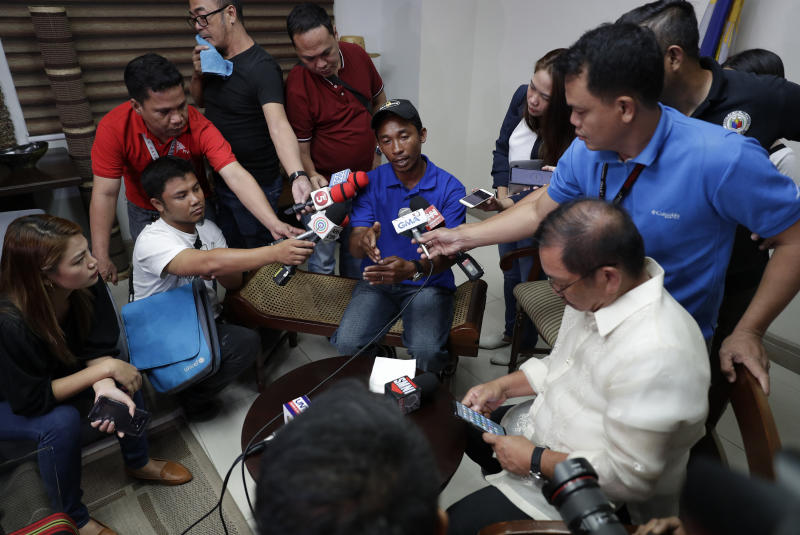 Reporters interview a crew of Filipino fishing vessel F/B Gimver 1, Richard Blaza, center, during a press conference at the Department of Agriculture in metropolitan Manila, Philippines on Monday, June 17, 2019. China recently acknowledged it's fishing vessel hit a Filipino boat in the disputed South China Sea in an incident that prompted an outcry in the Philippines but denies the collision was intentional. The Philippines has filed a diplomatic protest after Filipino fishermen said a Chinese vessel rammed their anchored boat on Sunday night then abandoned them as the boat sank in the Reed Bank. (AP Photo/Aaron Favila)