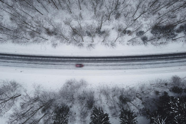 A car drives over the country road 497 between Silberborn and Holzminden, Germany, Sunday, Jan. 17, 2021. In the district of Holzminden, the largest and most frequented toboggan slopes are closed due to the Corona pandemic. (Swen Pfoertner/dpa via AP)