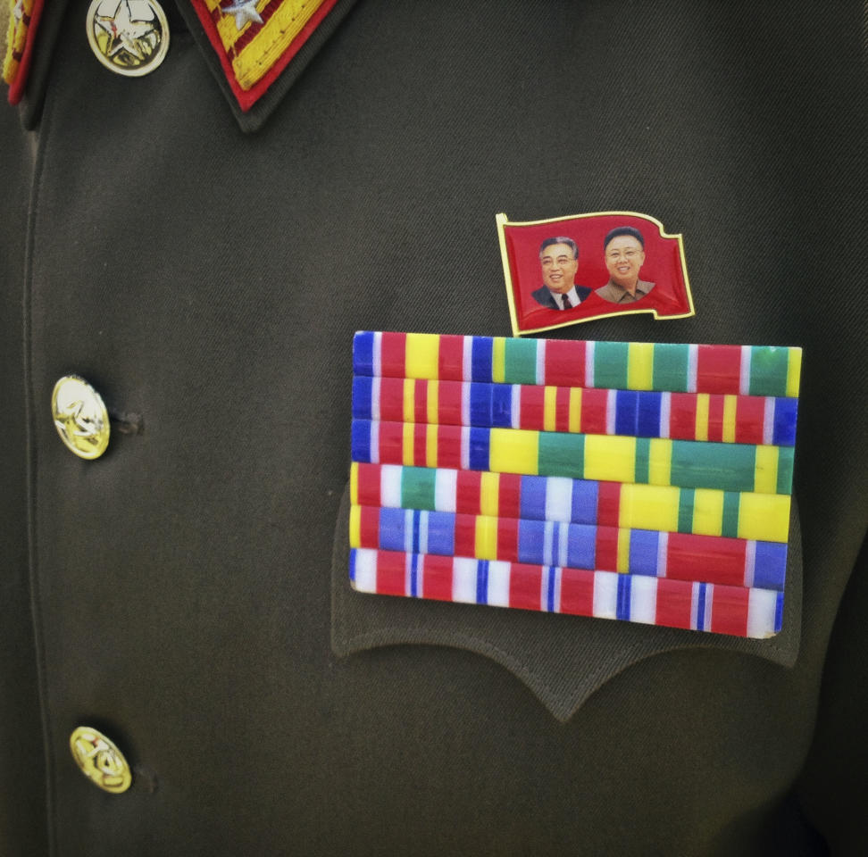 In this April 27, 2013 photo, a flag pin showing the late North Korean leaders is pinned next to military bars of a North Korean soldier's uniform near the demilitarized zone separating the two halves of the Korean peninsula near Panmunjom, North Korea. (AP Photo/David Guttenfelder)
