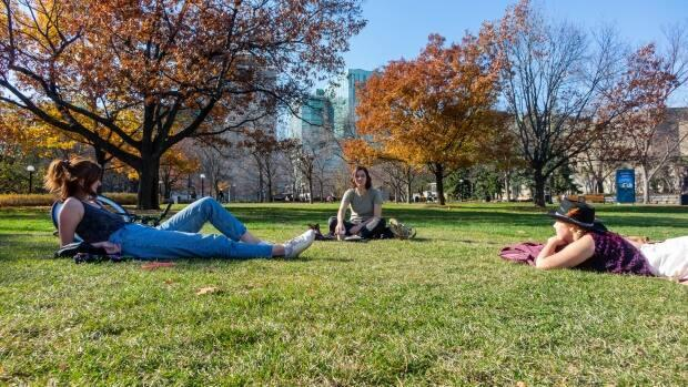 People lounge in Ottawa's Confederation Park on Nov. 5, 2020. Outdoor gatherings are capped at five people under the stay-at-home order.