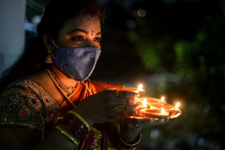A Hindu devotee wears a mask as she places earthen lamps or 'diyas' at her home on the eve of Diwali