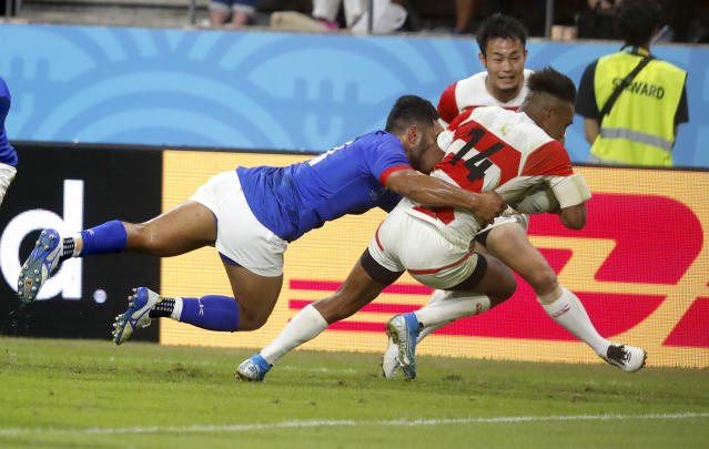 Japan's Kotaro Matsushima dives to score a try as he is tackled during the Rugby World Cup Pool A game at City of Toyota Stadium between Japan and Samoa in Tokyo City, Japan, Saturday, Oct. 5, 2019. Japan defeated Samoa 38-19.(AP Photo/Shuji Kajiyama)