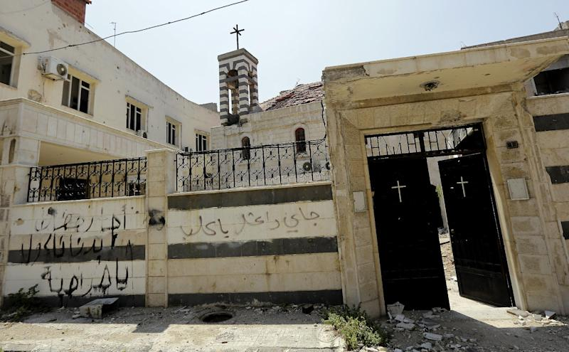 "Graffiti reading in Arabic, ""Beware you dogs, ISIL is coming "", on the external wall of the church of Umm al-Zunnar in Homs on May 12, 2014 (AFP Photo/Joseph Eid)"