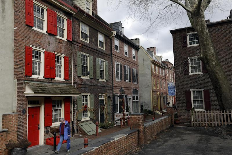 FILE - In this Feb. 27, 2013 file photo a person walks through Elfreth's Alley in Philadelphia. The City of Brotherly Love is perhaps best known for its Colonial roots but locals will tell you there's much more to explore in this city of 1.5 million people. (AP Photo/Matt Rourke, File)