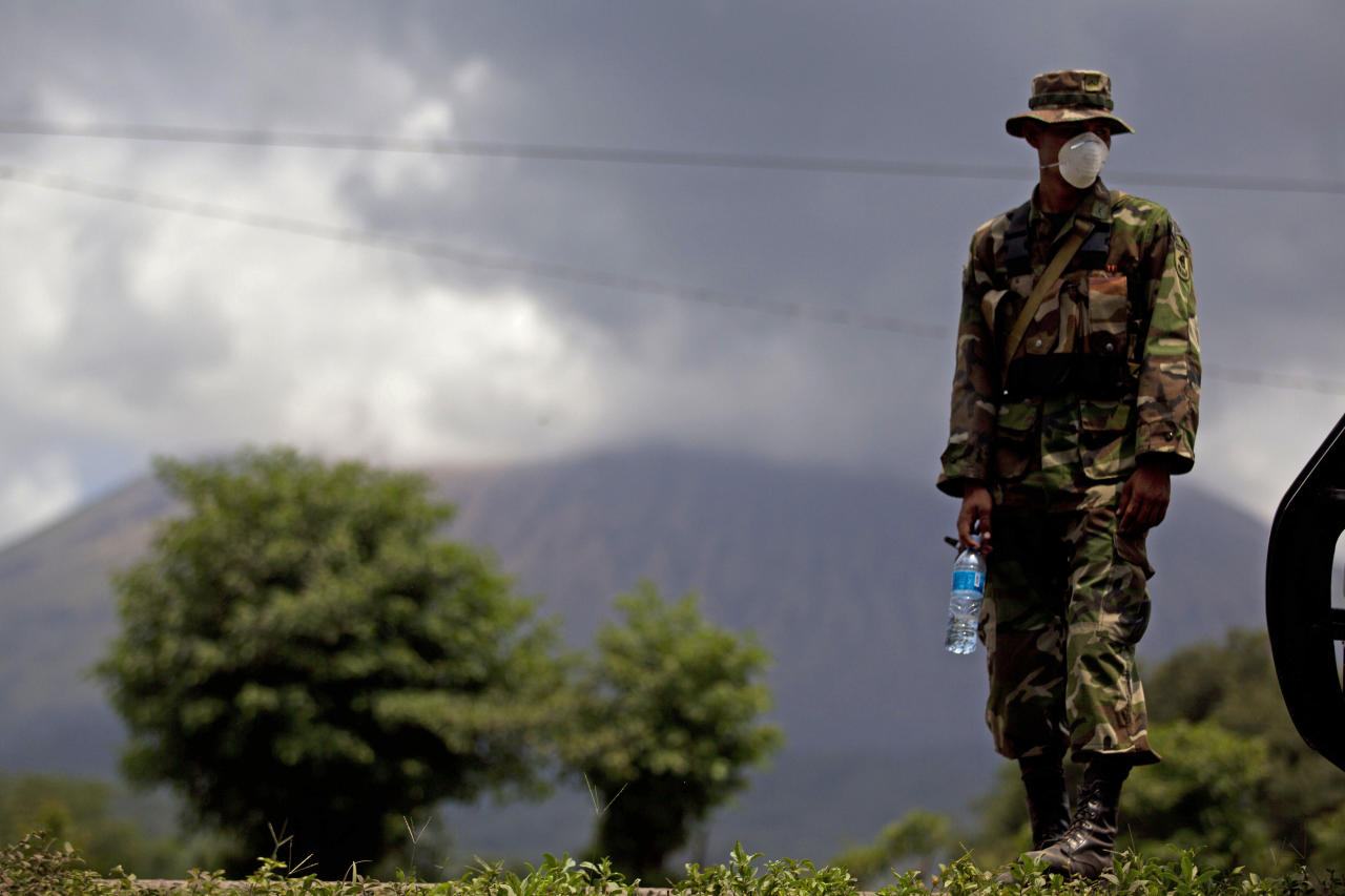 A Nicaraguan soldier wears a protective mask as the San Cristobal volcano, in background, spews smoke and ash, near Chinandega, Nicaragua, Saturday, Sept. 8, 2012. Nicaragua's tallest volcano, located about 70 miles (110 kilometers) northwest of Managua, near the Honduran border, has let off a series of explosions, spewing gases and showering ash on nearby towns, prompting an evacuations of residents. (AP Photo/Esteban Felix)