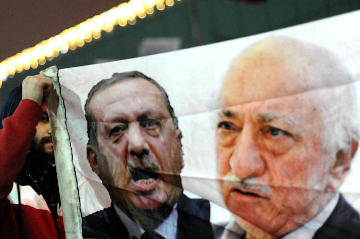 A Turkish protester holds up a banner with pictures of Recep Tayyip Erdogan (left) and US-based cleric Fethullah Gulen during a 2013 anti-government demonstration in Istanbul (AFP Photo/Ozan Kose)