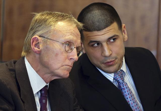 Aaron Hernandez (R) chats with his lawyer Charles Rankin as he appears for a pre-trial hearing at Bristol County Superior Court in Fall River, Massachusetts February 7, 2014. A Massachusetts judge on Friday denied a request by prosecutors for recordings of phone calls made from prison by the former National Football League star, who is awaiting trial in a 2013 murder of Odin Lloyd. REUTERS/Jonathan Wiggs/Boston Globe/Pool (UNITED STATES - Tags: CRIME LAW)
