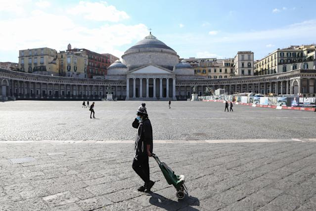 A person wearing a respiratory mask as part of precautionary measures against the spread of the new COVID-19 coronavirus, walks across a deserted Piazza del plebiscito in Naples on March 10, 2020. (Credit: Carlo Hermann/AFP)