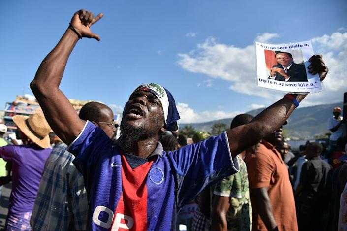 A demonstrator holds a picture of former Haitian President Jean Bertrand Aristide during a march of opposition political parties, in Port-au-Prince, on February 12, 2016 (AFP Photo/Hector Retamal)