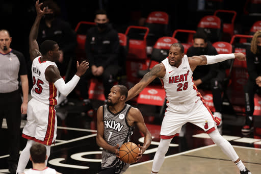 Brooklyn Nets forward Kevin Durant (7) drives to the basket between Miami Heat forward Andre Iguodala (28) and guard Kendrick Nunn during the first half of an NBA basketball game Monday, Jan. 25, 2021, in New York. (AP Photo/Adam Hunger)