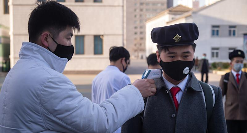 A student wearing a face mask undergoes a temperature check as he arrives for a lecture on preventative measures against the COVID-19 novel coronavirus at the Pyongyang University of Medicine.
