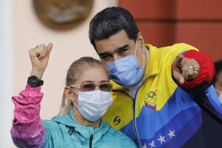 Venezuelan President Nicolas Maduro points to supporters during an event with his wife Cilia Flores marking Youth Day at Miraflores presidential palace in Caracas, Venezuela, Friday, Feb. 12, 2021, amid the COVID-19 pandemic. The annual holiday commemorates young people who accompanied heroes in the battle for Venezuela's independence. (AP Photo/Ariana Cubillos)