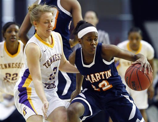 Tennessee Martin guard Jasmine Newsome (12) keeps the ball from Tennessee Tech guard Lashay Davis (13) in the first half of the championship game in the Ohio Valley Conference NCAA college basketball tournament on Saturday, March 9, 2013, in Nashville, Tenn. (AP Photo/Wade Payne)