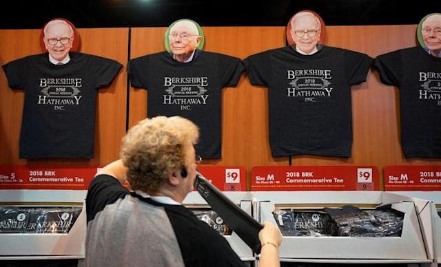 A worker arranges a display of t-shirts with images of Warren Buffett and Charlie Munger at the Berkshire Hathaway Inc annual meeting, the largest in corporate America, in its hometown of Omaha, Nebraska. REUTERS/Rick Wilking