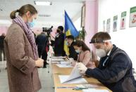 An election official checks a voter's information at a polling station during the second round of a presidential election in Chisinau