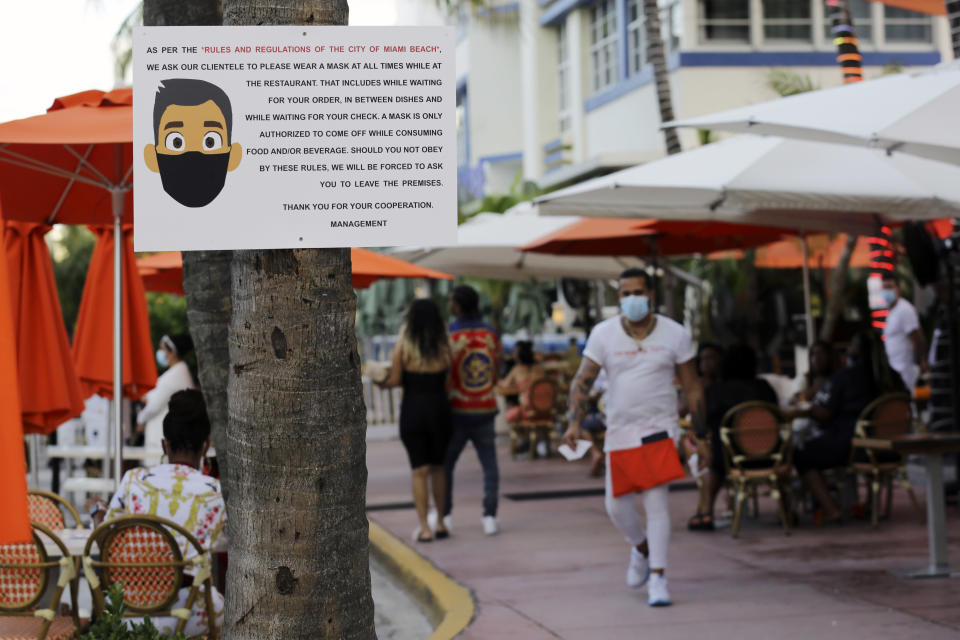A sign informs customers at the Edison Hotel restaurant about wearing a protective face mask during the coronavirus pandemic, Friday, July 24, 2020, along Ocean Drive in Miami Beach, Fla. Masks are mandated both indoors and outdoors in Miami Beach. People found not wearing a mask are subject to a civil fine of $50. (AP Photo/Lynne Sladky)