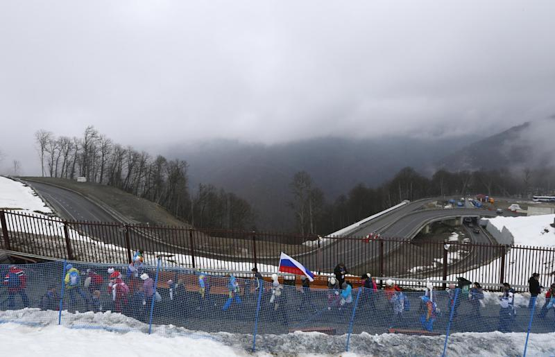 Spectators leave the venue after the men's snowboard cross competition was cancelled due to fog at the Rosa Khutor Extreme Park, at the 2014 Winter Olympics, Monday, Feb. 17, 2014, in Krasnaya Polyana, Russia. (AP Photo/Sergei Grits)