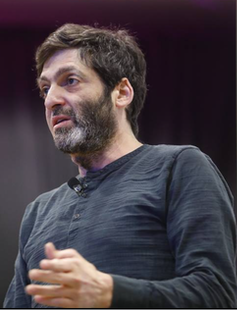 A picture of psychologist Dan Ariely giving a talk.