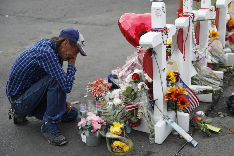 Tragedy: Basco cries beside a cross at a makeshift memorial near the scene of a mass shooting at a Walmart in El Paso