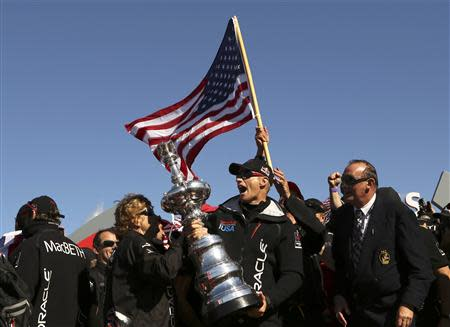 Skipper James Spithill celebrates with the America's Cup with members of the Oracle Team USA after winning the overall title of the 34th America's Cup yacht sailing race over Emirates Team New Zealand in San Francisco