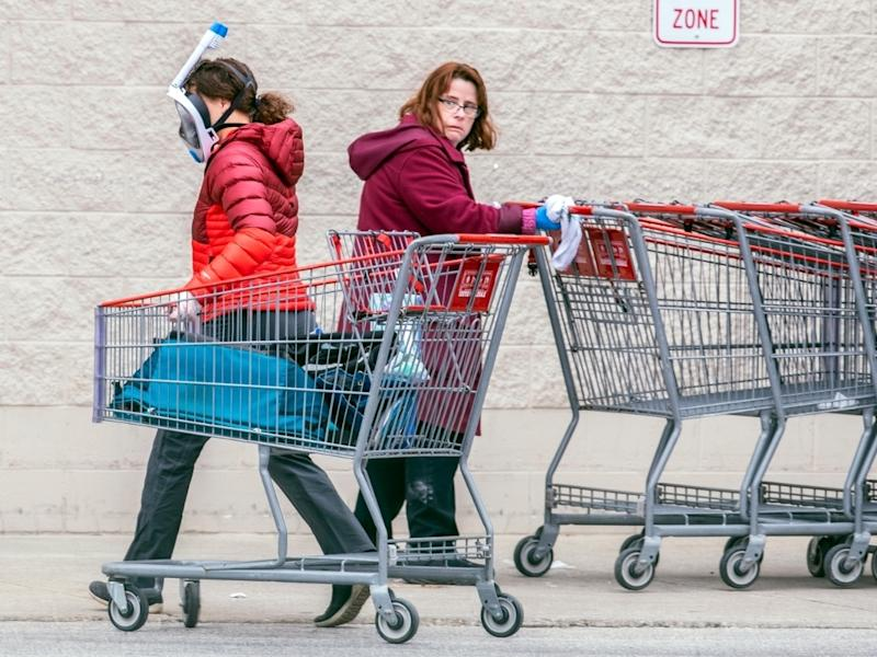 A Costco employee, right, looks towards a shopper wearing a mask and snorkel to go shopping, as she sanitizes carts that are returned from the parking lot to help reduce the spread of coronavirus.
