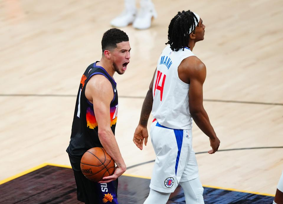 Phoenix Suns guard Devin Booker celebrates next to Los Angeles Clippers guard Terance Mann in the closing seconds of Game 1.