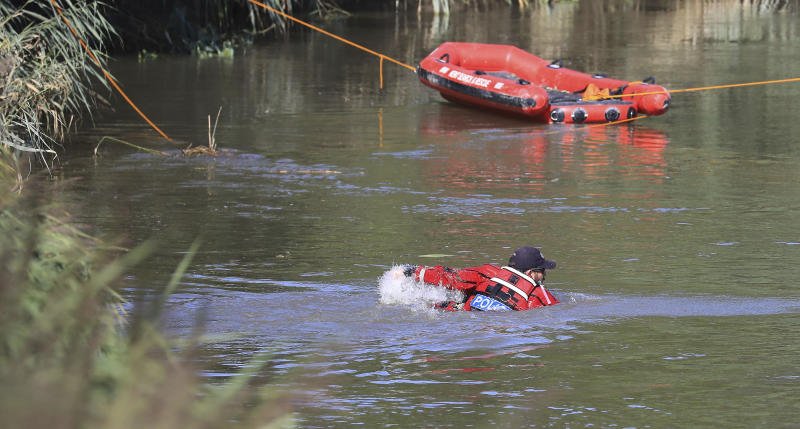 "A police officer enters a section of the River Stour during search operations for the missing six-year old boy, Lucas Dobson, who fell into the river Saturday and was swept away while on a fishing trip with family members, in Sandwich, southern England, Monday Aug. 19, 2019. The search for the six-year-old boy resumed Monday, but police have said it is ""unlikely"" he will be found alive. (Gareth Fuller/PA via AP)"