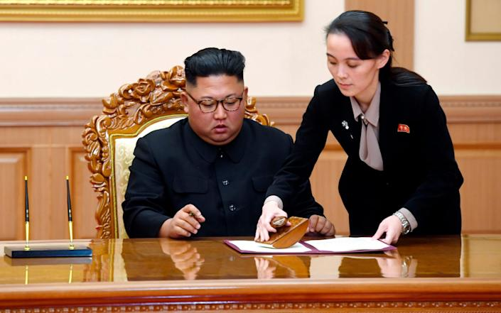 Kim Yo Jong, right, helps her brother North Korean leader Kim Jong Un sign a joint statement - Pyongyang Press Corps Pool