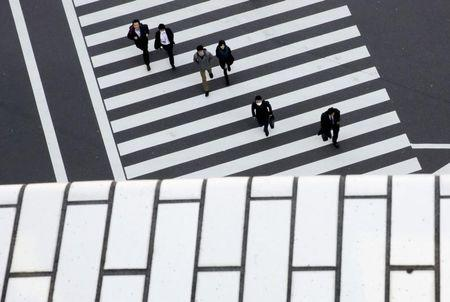 FILE PHOTO - People cross a street in a business district in Tokyo