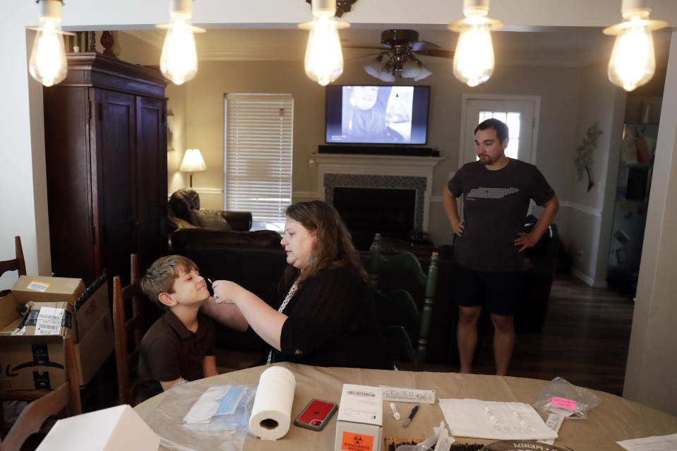Mendy McNulty swabs the nose of her son, Hudson, 9, in their home in Mount Juliet, Tenn., Tuesday, July 28, 2020. Her husband, Joe, right, waits his turn. The family is participating in testing done twice a month to help answer some of the most vexing questions about the coronavirus. (AP Photo/Mark Humphrey)