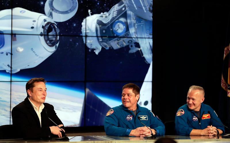 Elon Musk, left, CEO of SpaceX, speaks accompanied by NASA astronauts Bob Behnken, center, and Doug Hurley during a news conference - John Raoux/AP