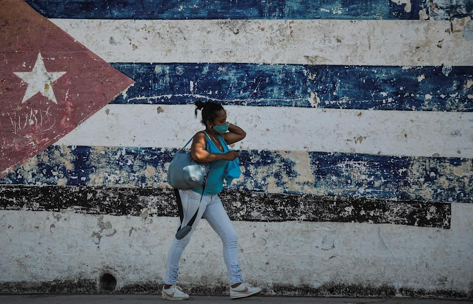 A woman walks near a wall depicting the Cuban flag in Havana as the UN meets in New York (AFP via Getty Images)