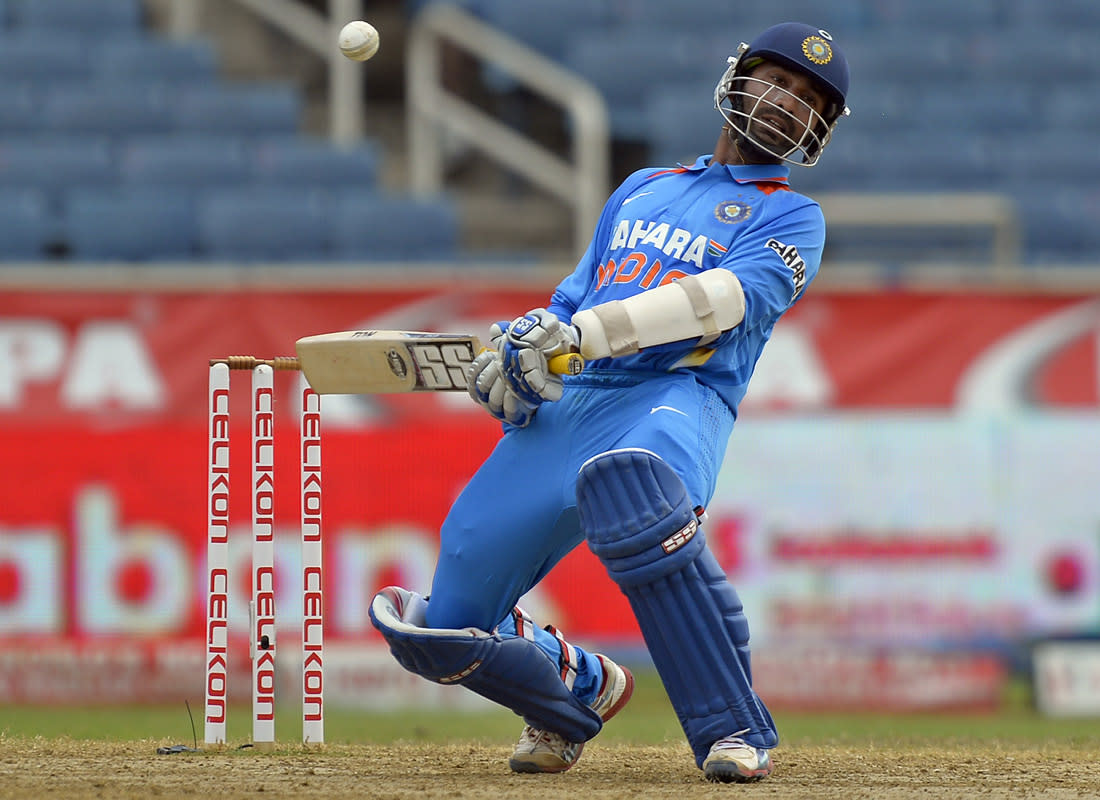 Indian cricketer Dinesh Karthik avoids a bouncer during the third match of the Tri-Nation series between India and Sri Lanka at the Sabina Park stadium in Kingston on July 2, 2013. Sri Lanka have scored 348/1 at the end of their innings. AFP PHOTO/Jewel Samad