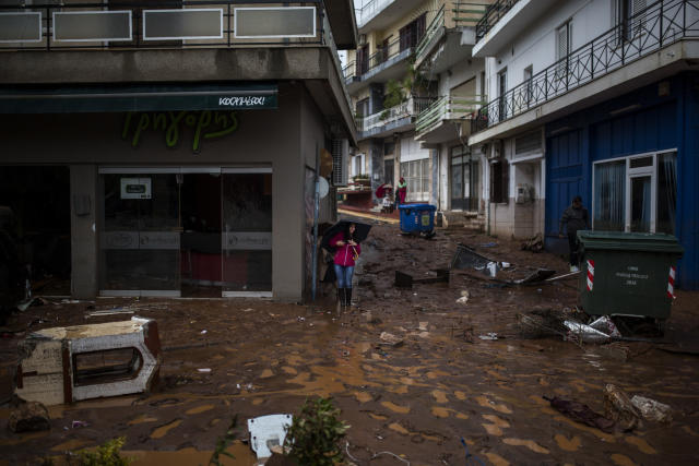 A woman with an umbrella stands in a flooded street next to a damaged shop. (Angelos Tzortzinis/AFP/Getty Images)