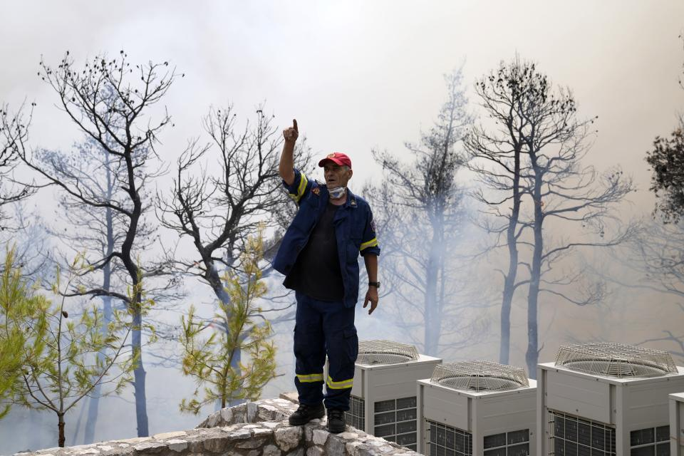 A firefighter instructs his colleagues during a wildfire in Ippokratios Politia village, about 35 kilometres (21 miles) north of Athens, Greece, Friday, Aug. 6, 2021. Thousands of people fled wildfires burning out of control in Greece and Turkey on Friday, as a protracted heat wave turned forests into tinderboxes and flames threatened populated areas, electricity installations and historic sites. (AP Photo/Thanassis Stavrakis)
