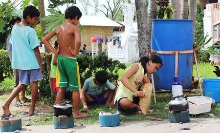 Residents cook their meals on higher ground after evacuating their homes due to super-typhoon Hagupit in Tacloban city, central Philippines December 5, 2014. REUTERS/Rowel Montes