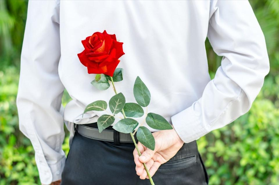 Man holding a red rose behind his back