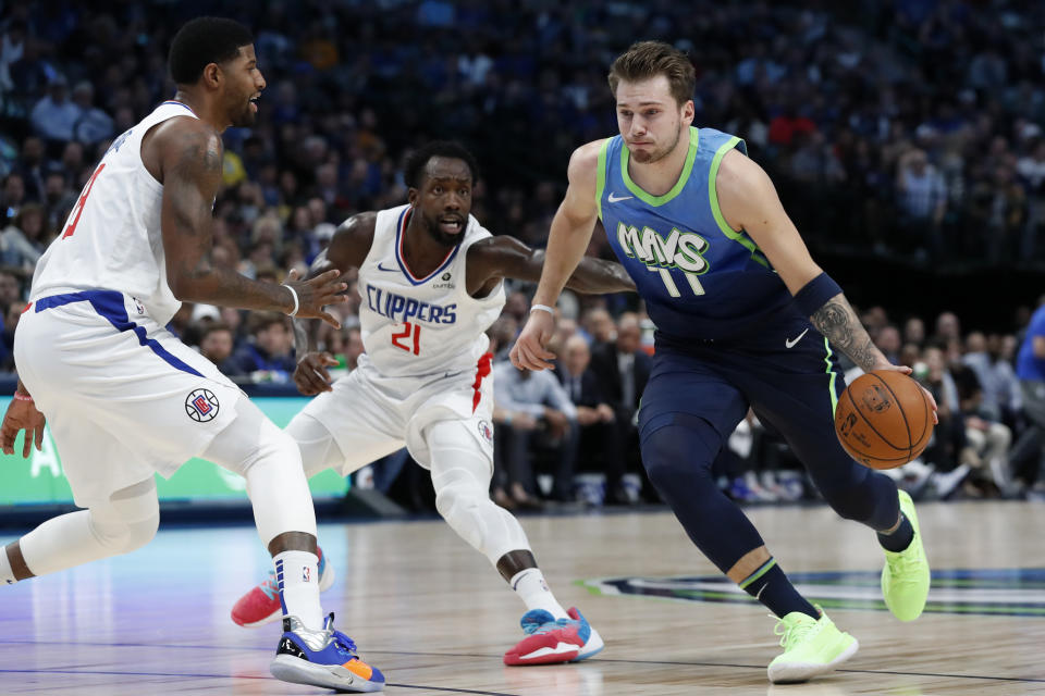 Los Angeles Clippers forward Paul George, left, and Patrick Beverley (21) defend as Dallas Mavericks forward Luka Doncic (77) drives to the basket in the first half of an NBA basketball game in Dallas, Tuesday, Nov. 26, 2019. (AP Photo/Tony Gutierrez)