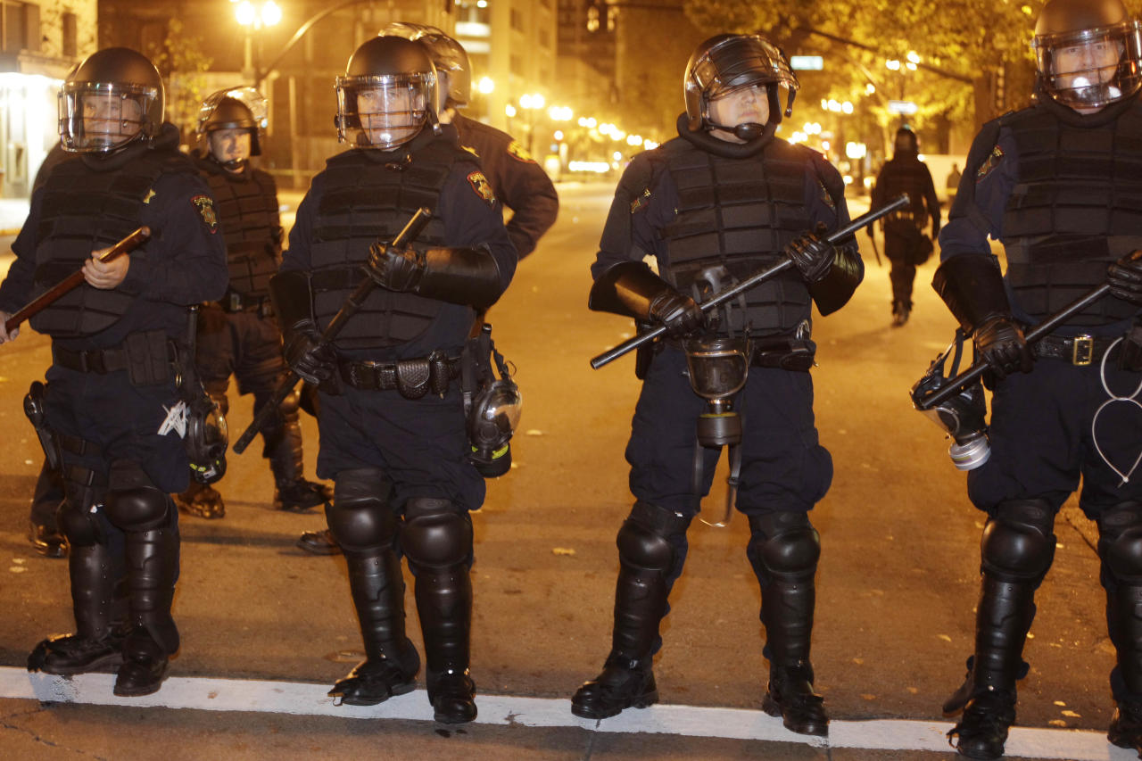 A line of police stand staged at an Occupy Oakland encampment in Oakland, Calif., early Monday, Nov. 14, 2011. (AP Photo/Paul Sakuma)