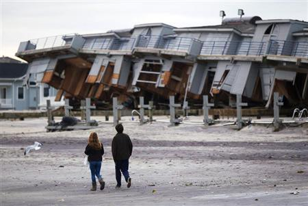 People walk past a beach club destroyed by Hurricane Sandy in Sea Bright, New Jersey