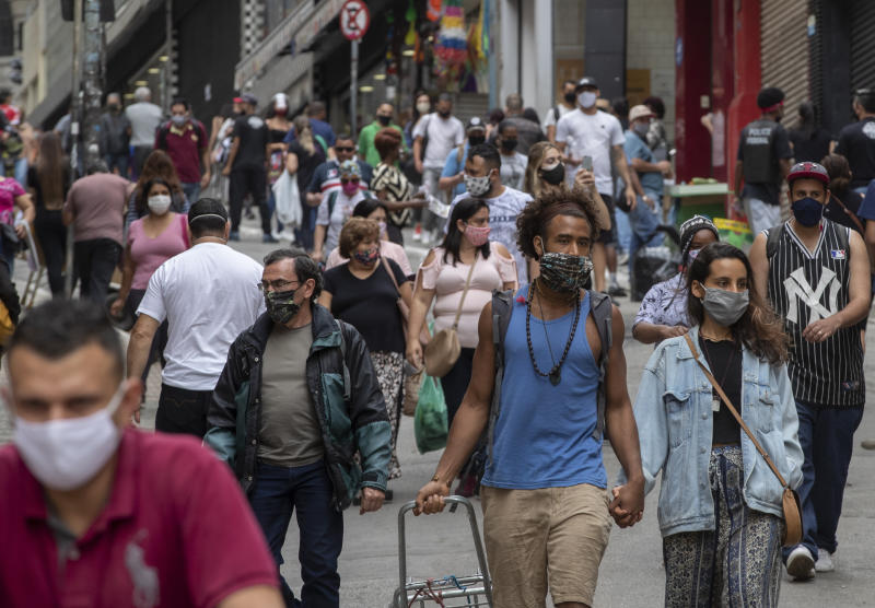 People walk through a downtown shopping district in Sao Paulo, Brazil, Wednesday, June 10, 2020. Retail shops reopened on Wednesday in Brazil's biggest city after a two-month coronavirus pandemic shutdown that aimed to contain the spread of the new coronavirus. (AP Photo/Andre Penner)