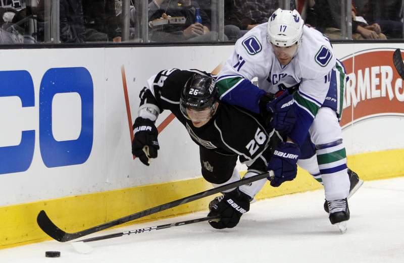 Los Angeles Kings defenseman Slava Voynov (26), of Russia is knocked to the ice by Vancouver Canucks center Ryan Kesler (17) during the first period of Game 3 in a first-round NHL Stanley Cup playoff series in Los Angeles, Sunday, April 15, 2012. (AP Photo/Alex Gallardo)