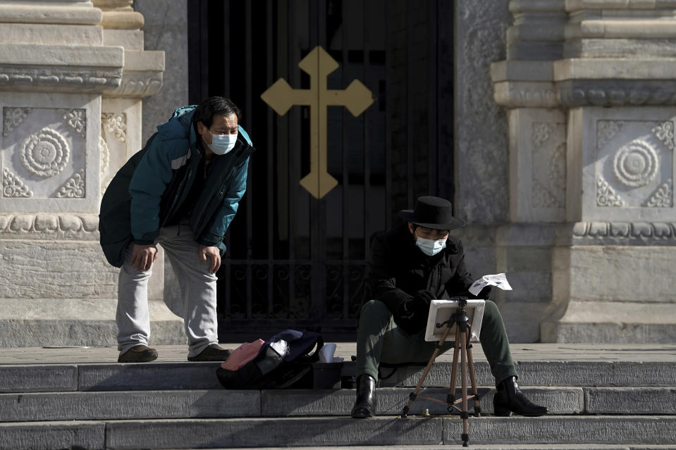 A man wearing a face mask to help curb the spread of the coronavirus looks at a masked man drawing outside a church in Beijing, Monday, Jan. 18, 2021. A Chinese province grappling with a spike in coronavirus cases is reinstating tight restrictions on weddings, funerals and other family gatherings, threatening violators with criminal charges. (AP Photo/Andy Wong)