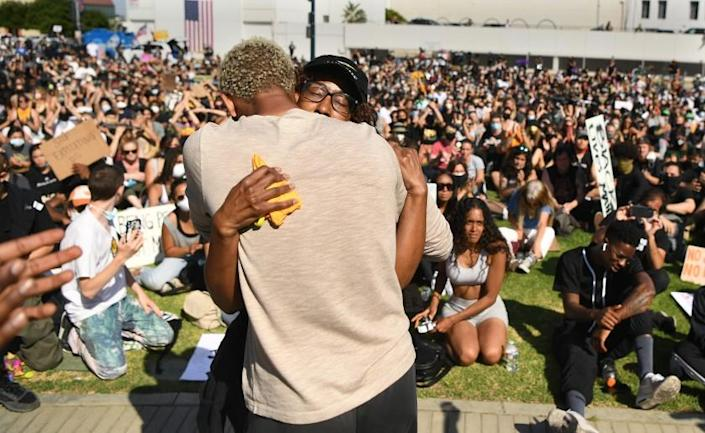 BEVERLY HILLS, CALIFORNIA JUNE 6, 2020-A family member of Breonna Taylor, right, is hugged by another woman after speaking to protestors in Beverly Hills Saturday. The protest was organzied by the Refuse Fascism group. (Wally Skalij/Los Angeles Times)